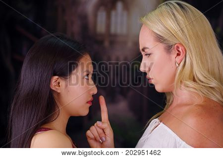 Young mad american blonde woman, putting her finger in the mouth of a foreign woman, pretending to keep her in silence of violence and racism. Racism, violence or discrimination concept in a blurred background.