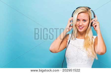 Happy young woman with headphones on a blue background