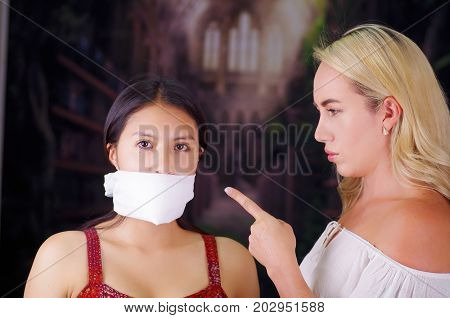 Young mad american blonde woman, exhorting to a latin woman to leave the country, using her hand and pointing to her, while foreign woman is with a white thing covering her mouth, racism, violence or discrimination concept.