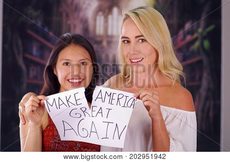 Two young women blonde and latin girl smiling and breaking racism idiosyncrasy from a american person and foreign people, destroying a paper that is written make america great again, racism, violence or discrimination concept.