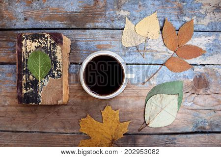 Vintage books, cup of coffee and autumn leaves on wooden desk.