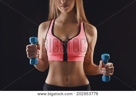 Fitness model woman with dumbbells on black studio background. Young girl in fitwear with sport equipment. Bodybuilding, healthy lifestyle concept