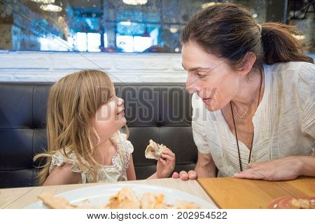 Three years old blonde girl with pizza portion in hand talking to woman mother sitting in black couch in restaurant