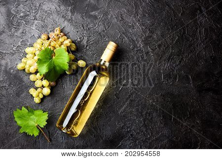 Bottle of white wine with grapes and leaves of grapes on dark concrete background.