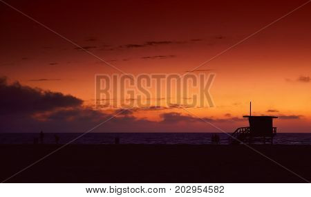 Lifeguard tower at sunset in Hermosa Beach Los Angeles California in the background calm water