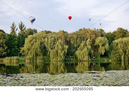 BILA TSERKVA UKRAINE - AUGUST 25: The view on balloons are over Olexandria Park and visitors on August 25 2017 in Bila Tserkva Ukraine. The balloons show is dedicated to Ukrainian Independence Day.