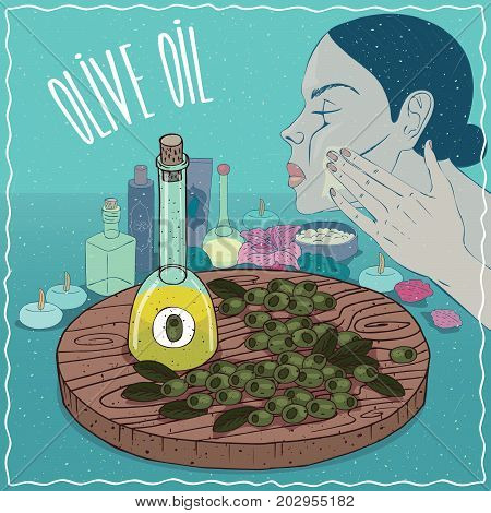 Glass Decanter of Olive oil and fruits of Olea europaea plant. Girl applying facial mask on face. Natural vegetable oil used for skin care