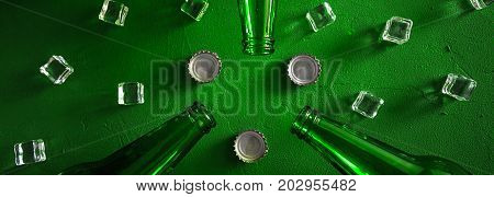 Conceptual beer background. Green beer bottles with ice cubes and lids on a green background, border design panoramic banner