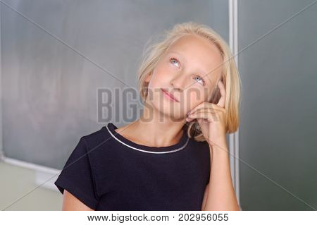 Adorable blond kid girl thoughtful in a classroom near a chalkboard. The child is focused and attentive remembers, looking up thoughtfully. Back to school.