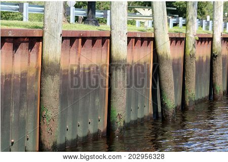 A metal bulkhead with pilings at low tide.