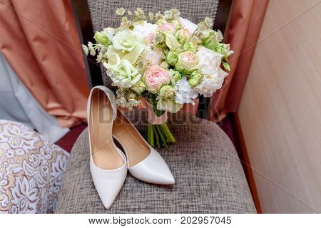 Close Up Of Beautiful Wedding Bouquet Of Pink And White Roses And Bride Shoes On Chair Indoors. Wedd