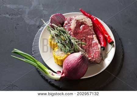 Raw rib eye steak with herbs and vegetables. Cooking ingredients for restaurant dish. Fresh meat, onion, chilli, corn on plate on dark background.