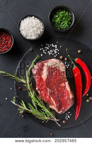 Raw rib eye steak with herbs and spices. Cooking ingredients for restaurant dish. Fresh meat with chilli on plate on black background, top view