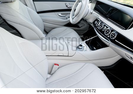 White leather interior of the luxury modern car. Leather comfortable white seats and multimedia. Steering wheel and dashboard. Automatic gear stick. Modern car interior details