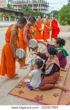Vang Vieng, Laos - January 21, 2017: Buddhist monks collecting alms in the morning in Vang Vieng, Laos