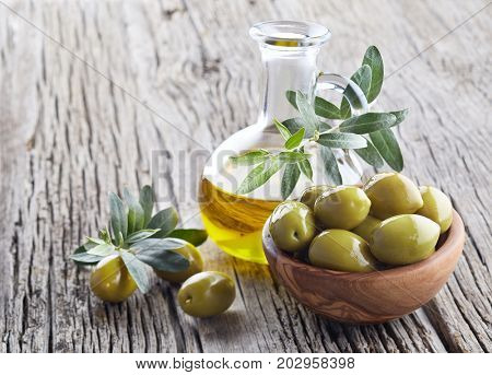 Virgin olive oil and green olives on wooden board