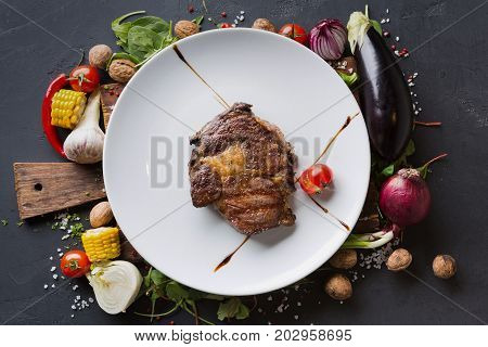 Rib eye steak on white plate on wooden desk with vegetables and spices border on dark background, top view.