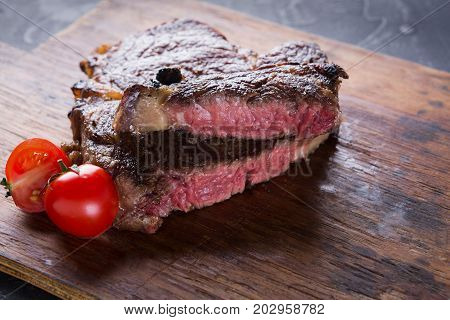 Rare rib eye steak on wooden board decorated with tomatoes, closeup