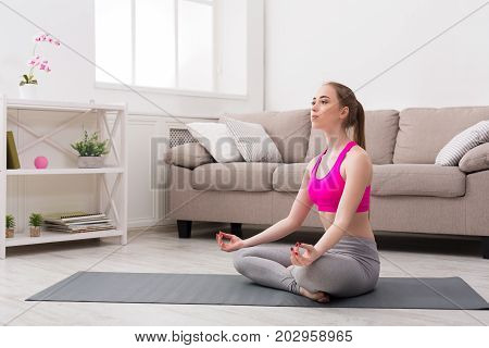 Fitness, woman yoga relax meditation in lotus pose at home. Young slim girl makes exercise.