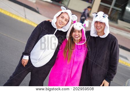 Close up of a happy group of friends wearing different costumes, one woman wearing a pink unicorn costume, other woman a panda costume and the man wearing a cat costume, in the city of Quito, Ecuador.