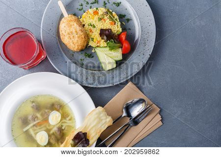 Healthy food background, restaurant business lunch top view. Noodle soup, vegetable risotto with chicken cutlet, refreshing berry drink on gray table, cutlery and empty business card for copy space
