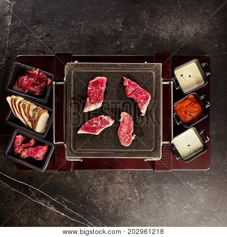 Meat platter on black stone and cups with three kinds of sauces sprinkled with herbs. Gastronomic restaurant menu
