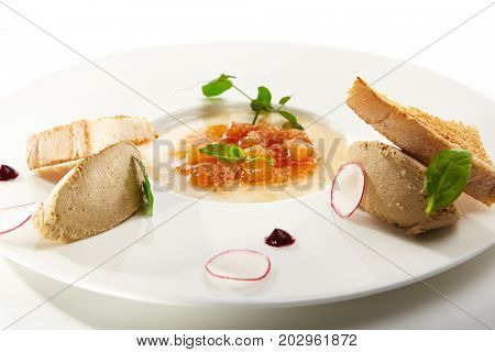 Pate of fowl with toast and citrus jam with radish slices and fresh herbs on flat white plate. Gastronomic restaurant menu