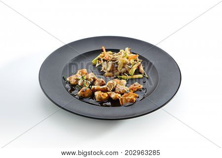 Teppanyaki Japanese and Korean Grill Food - Chicken with vegetables poured with sauce and sprinkled with fresh herbs and sesame seeds on black plate on  white isolated background