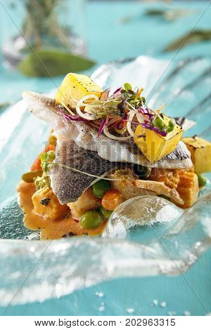 Fillet of Dorado with vegetables with green peas sauce and herbs in  beautiful glass plate. Gastronomic restaurant menu