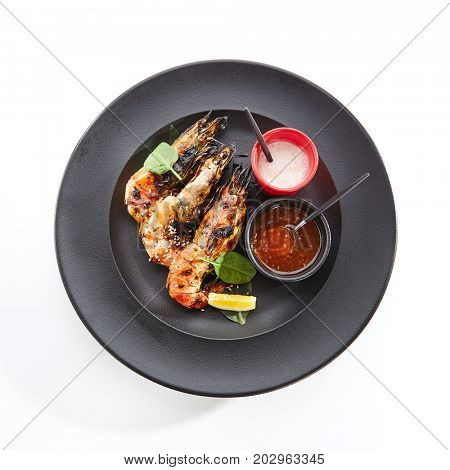 Teppanyaki Japanese and Korean Grill Food - 6/8 Shrimp Grill with fresh herbs and sauces on black plate. Top View