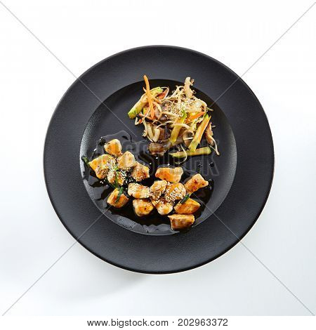Teppanyaki Japanese and Korean Grill Food - Chicken with vegetables poured with sauce and sprinkled with fresh herbs and sesame seeds on black plate on  white isolated background. Top View
