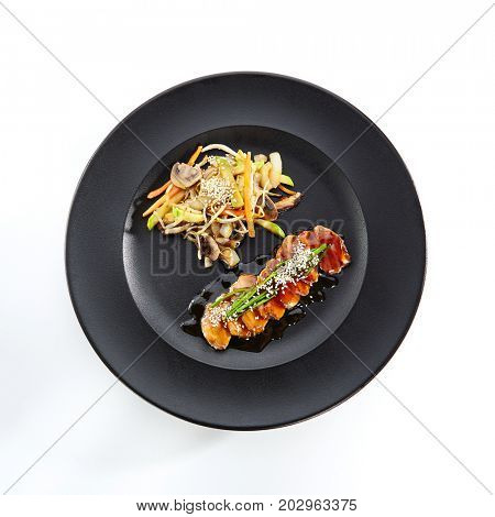Teppanyaki Japanese and Korean Grill Food - Duck Breast with Vegetables with mushrooms sprinkled with sesame seeds and fresh herbs in black plate on white isolated background
