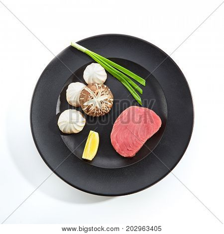 Teppanyaki Japanese and Korean Grill Food - Marbled beef with Mushrooms with fresh herbs and slice of lemon on black plate on white isolated background. Preparation of raw food for frying on teppan