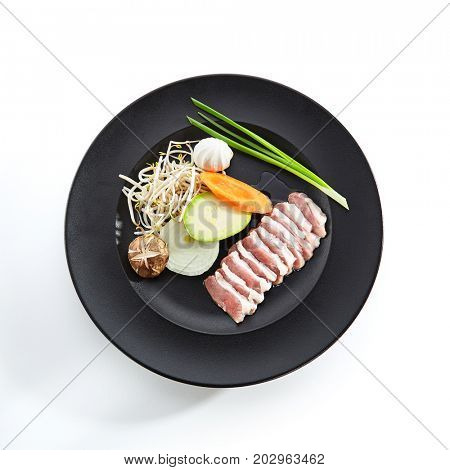 Teppanyaki Japanese and Korean Grill Food - Duck Breast with Vegetables with greens and mushrooms on black plate on white background. Preparation of raw ingredients for frying on teppan. Top View