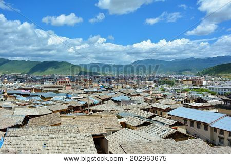 Shangri-la (zhongdian) City, Yunnan Province, China. Wooden Roofs Of The Tibetian Houses On The Fore