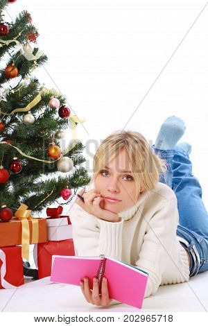 Beautiful young woman lying Christmas presents in front of tree over living room.