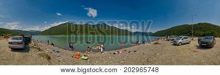 ANANURI, GEORGIA - 29 July 2017: Panorama of People relaxing on Zhinvali Lake Beach near Ananuri Castle in Georgia