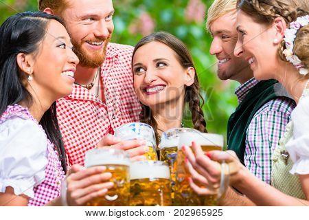 Five friends, men and women, having fun in beer garden clinking glasses with beer