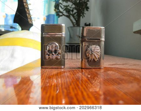 Two reusable lighters. Figure in the shape of a skull and in the shape of an Indian.