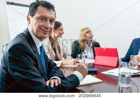 Portrait of a Hispanic middle-aged business man smiling and looking at camera with confidence, during a meeting in the conference room of a successful corporation