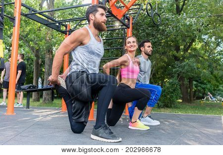 Full length side view of three determined friends doing stretching exercises for legs, as warming up or cool down routine outdoors in a modern fitness park