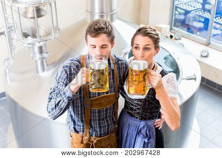 Brewer and woman toasting in beer brewery close to brewhouse