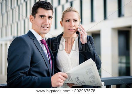 Business man and woman with paper and phone in front of office building in the city