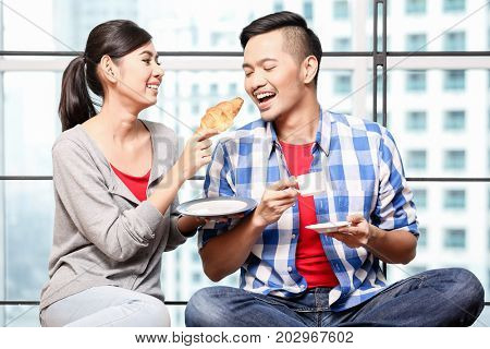 Young asian couple, woman and man, having breakfast together in skyscraper apartment