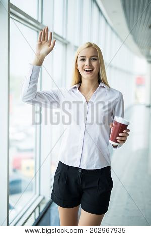 Businesswoman Welcomes With Cup Of Coffee In Other Hand Near Big Panoramic Window In The Office