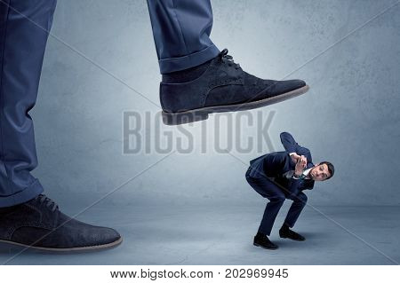 Young small businessman is trampled by a big foot in an empty space