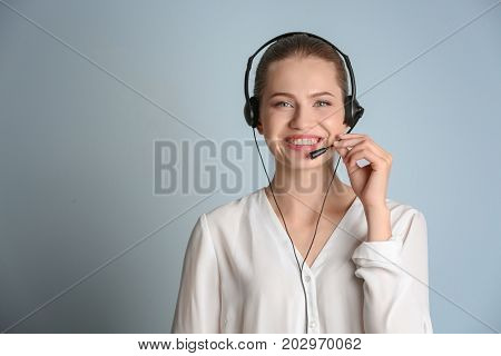 Beautiful young woman with headset on color background