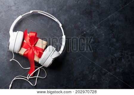 Music gift concept. Headphones and gift box on stone table. Top view with space for your greetings