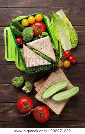Lunch box with vegetables and sandwich on wooden table. Take away food box. Top view