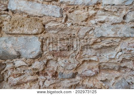 Stone wall of old limestone stones. Abstract texture background